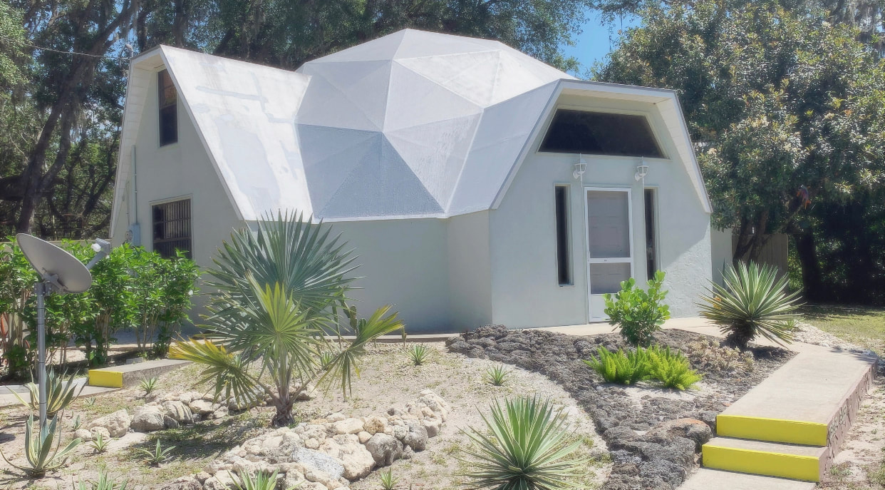 geodesic dome with white walls in front of a zeroscaping lawn